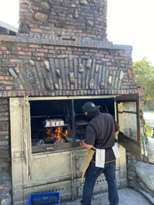 The Grill's Chef Placing Oxtails in the Chimney Smoker