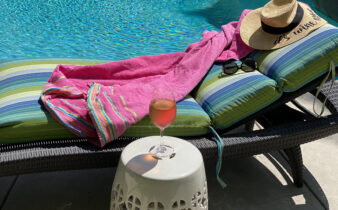 A glass of rosé next to a pool and lounge chair with sunglasses and straw hat