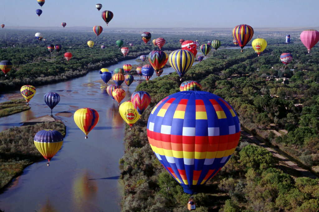 Hundreds of brightly colored balloons floating over the Rio Grande River by Ron Behrmann