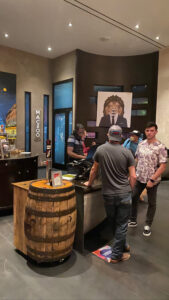 Men in lobby by Maceoo Clothing Store sign and beer keg